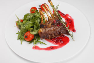 """Rack of lamb on a bed of arugula with pomegranate sauce and tomatoes """"Cherry"""""""