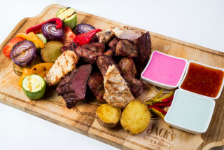 Plate of four meats and grilled vegetables