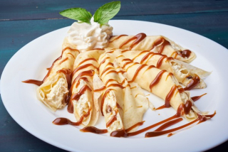 Sweet thin pancakes (crêpe) stuffed with cottage cheese and topped with caramel