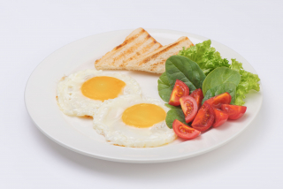 Fried eggs with mix salad and cherry tomatoes