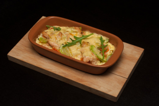 Salmon baked in creamy sauce with zucchini, carrots and leek