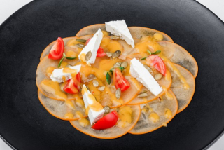 Carpaccio of persimmon with sheep cheese and cherry tomatoes