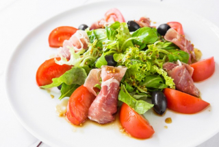Mix salad with prosciutto, tomatoes and dried olives