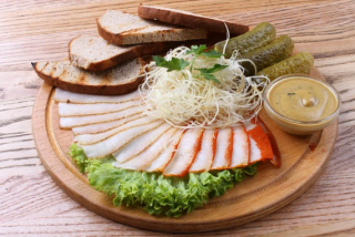 Нарезанное сало с солеными огурцами, горчичным соусом, ржаным хлебом, копченым сыром и зеленым салатом.