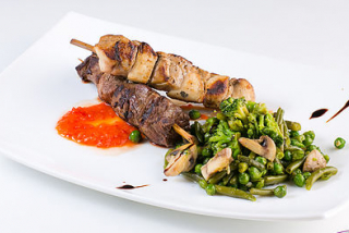 Skewers of chicken and beef with broccoli and green beans