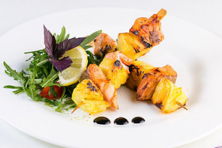 Skewers of salmon with pineapple and salad of arugula