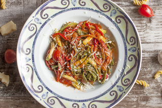 Spinach tagliatelle with delicious vegetables in italian tomato sauce