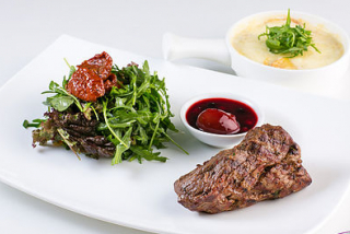 Veal steak with potato gratin and arugula