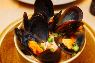 Thick soup with mussels and noodles in oriental styl